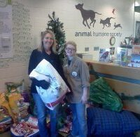 Two team members with dog food and other pet supplies
