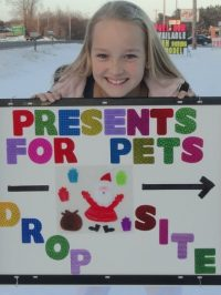 A little girl smiling with the presents for pets drop off sign