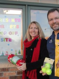 The vet and his wife smiling next to the presents for pets sign