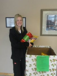 A team member next to a presents for pets donation box